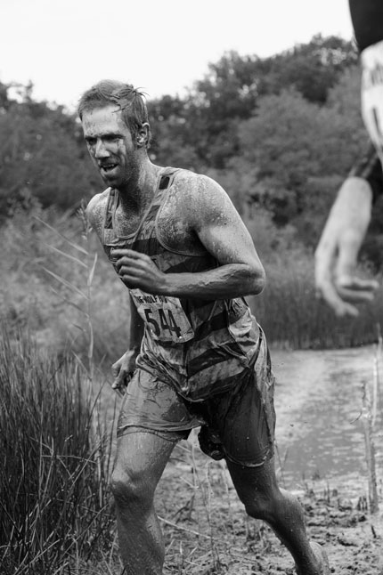 A man running covered in muddy water