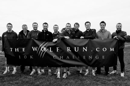 Team photo holding a Wolf Run banner